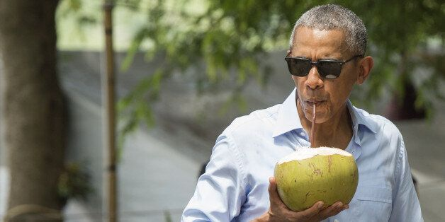 US President Barack Obama drinks from a coconut as he makes a surprise stop for a drink alonside the...
