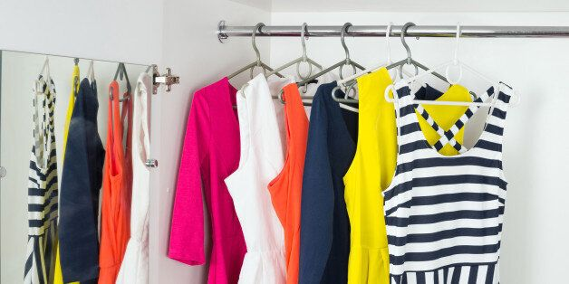 a series of bright modern fashion women's dresses on hangers in a white cupboard for summer and