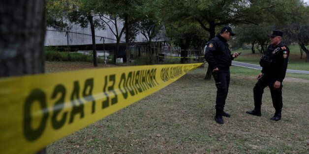 Police officers stand at a police line outside the Colegio Americano del Noreste after a student opened...