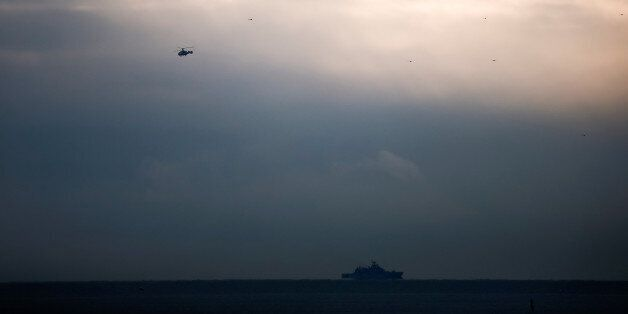 A helicopter flies next to a ship near the crash site of a Russian military Tu-154 plane, which crashed...
