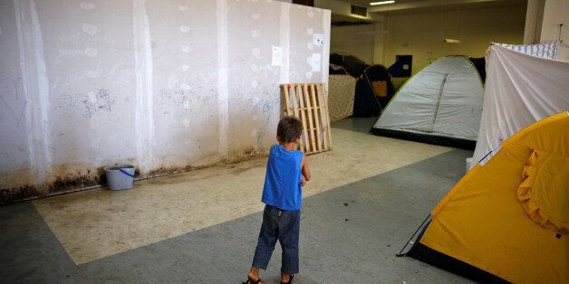 A boy makes his way inside the disused Hellenikon airport where refugees and migrants are temporarily...