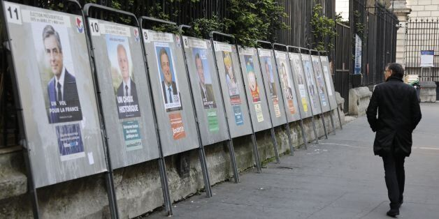 A pedestrian watches the candidates' official campaign posters on April 21, 2017 in Paris, two days before...