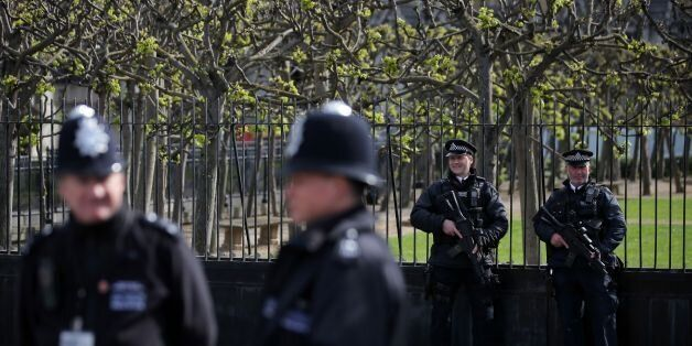 Armed British police officers (R) hold their weapons as they stand on duty outside the Houses of Parliament...