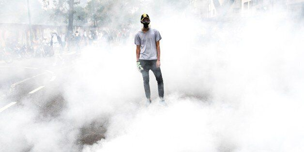 CARACAS, VENEZUELA - APRIL 10: Hooded activist standing on a tear gas curtain during clashes with the...