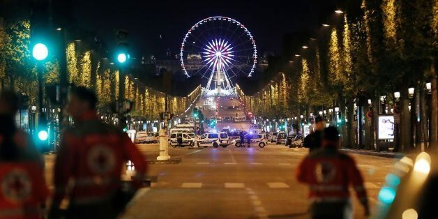 Rescuers walk on the Champs Elysees in Paris after a shooting on April 20, 2017.One police officer was...