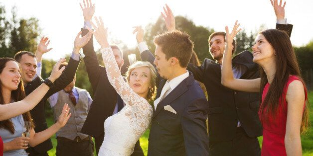 Full length portrait of newlywed couple dancing and having fun with bridesmaids and groomsmen in green...