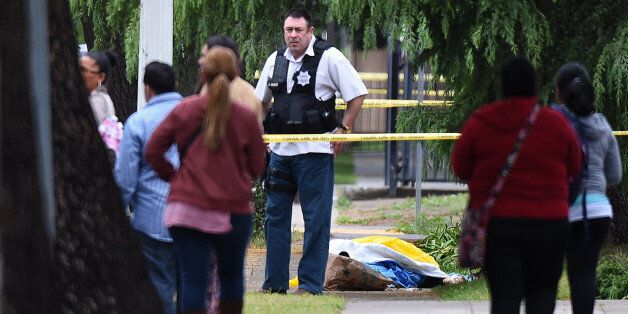 A Fresno police detective stands over the body of one of the three shooting victims as office workers...