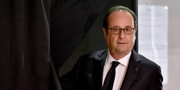 French President Francois Hollande exits a voting booth before casting his ballot in the first round...
