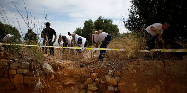 Members of Scotland Yard work at an area during the search for missing British girl Madeleine McCann...