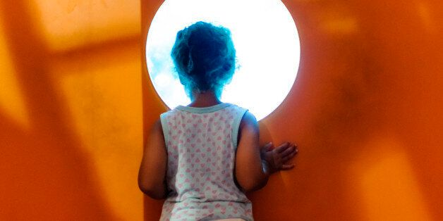 Cstock photo of little girl who is looking through a hole in a wall. She is looking into an aquarium....