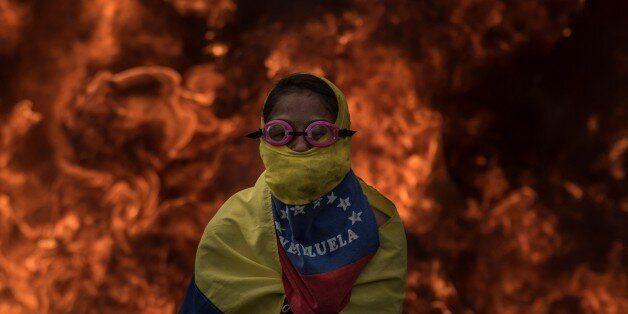 CARACAS, VENEZUELA - APRIL 24: Venezuelan opposition activist cover his face in front of burning barricades...