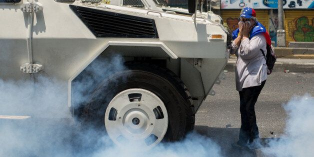 A woman block the police during a march against Venezuelan President Nicolas Maduro, in Caracas on April...