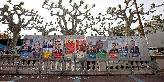 Campaign posters of the 11 candidates who run in the 2017 French presidential election are seen in Le...