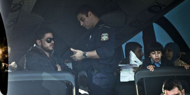 Greek police checks the documents of Syrian and Iraqi refugees aboard a bus taking them to the Greek-Macedonian...