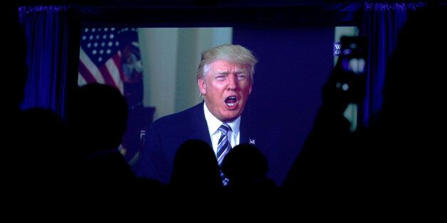 Guests watch a video of U.S. President Donald Trump as he addresses the 15th Plenary Assembly of the...