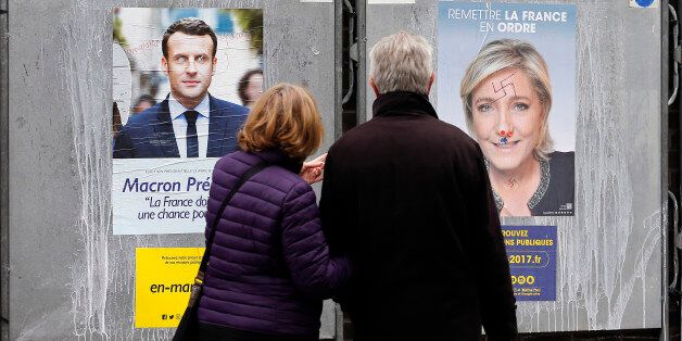 PARIS, FRANCE - APRIL 18: A couple look at graffitied official campaign posters of Marine Le Pen, French...