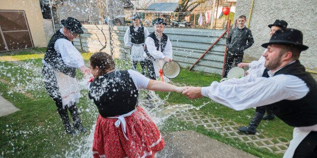 IAROVCE, SLOVAKIA - MARCH 28: Men seen throwing buckets of water on a woman as part of Easter celebrations...