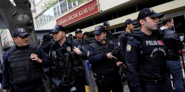 Riot police secure the entrance of the High Electoral Board as people wait in line to submit their personal...
