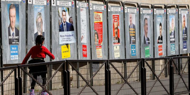 PARIS, FRANCE - APRIL 19: A child walks past official campaign posters for all eleven candidates for...