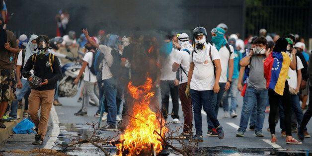 Demonstrators burn tire during a rally against Venezuela's President Nicolas Maduro in Caracas, Venezuela...