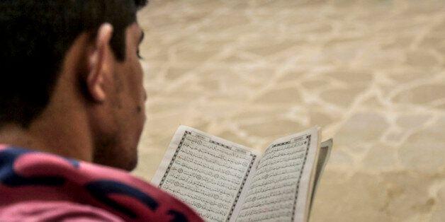 A prisoner reads the Koran inside Derick central prison, east of Syrian Kurdish city of Qamishli in Hasaka...