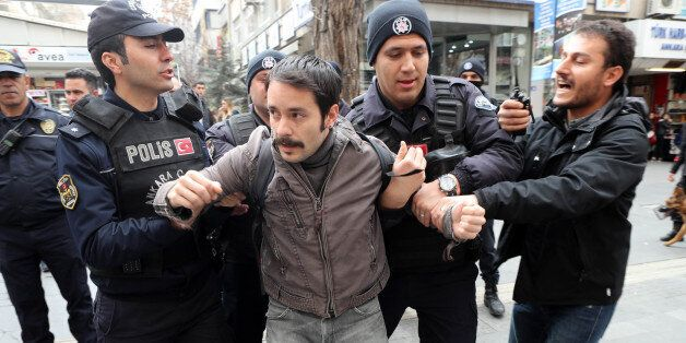 Turkish policemen arrest a protester during a demonstration on March 11, 2017 in Ankara.Turkish journalists...