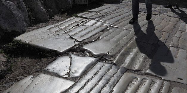 Street pavement (backlit view) made of ancient marble slabs just outside the Acropolis of Athens,