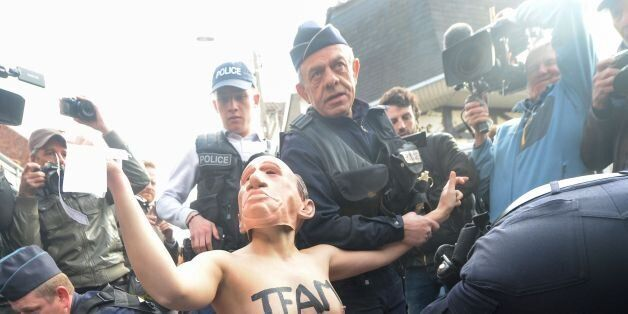 Members of feminist activist group Femen are detained by police officers as they protest against French...