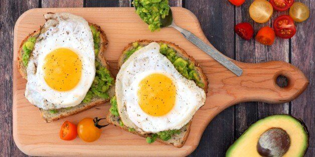 Avocado, egg open sandwiches on whole grain bread with tomatoes on paddle board with rustic wood table