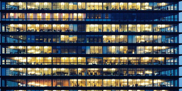 Lots of people working late. Employees seen as silhouettes against their brightly lit offices with large...