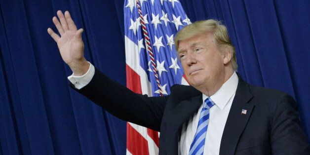 U.S. President Donald Trump waves during a town hall meeting with executives on the America business...