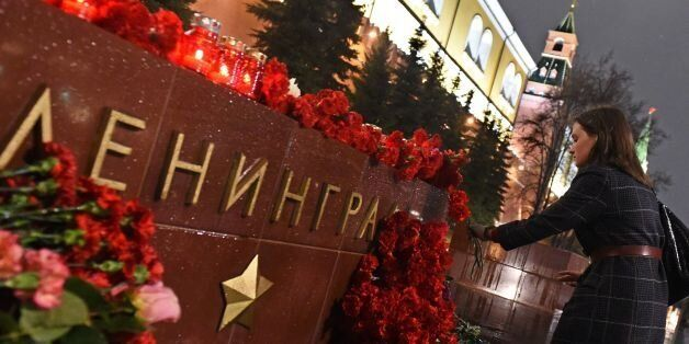 A woman lays flowers in memory of victims of the blast in the Saint Petersburg metro at a memorial stone...