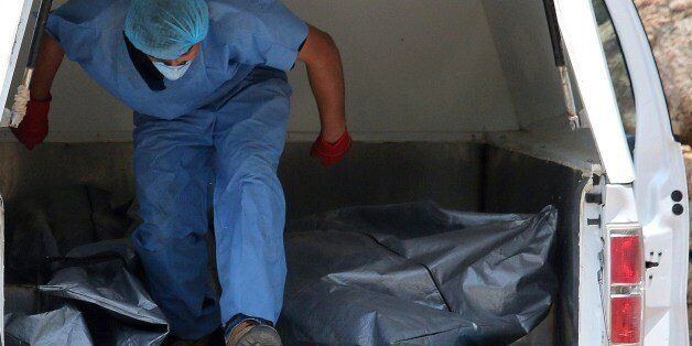 Forensic personnel load onto a van the body of one of the ten bodies found in clandestine graves in the...