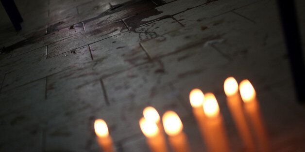 Candles are seen in front of the bloodstains of Rodrigo Quintana, who was killed last night by a rubber...