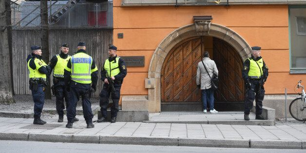 Police officers stand outside the Stockholm District Court as Uzbek national Rakhmat Akilov, prime suspect...