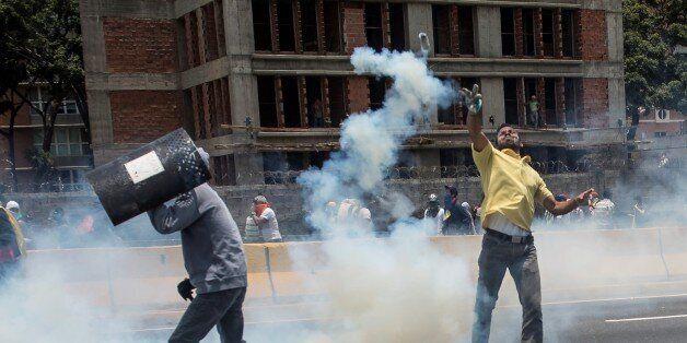 CARACAS, VENEZUELA - APRIL 10: Venezuelan opposition activists throwing back a tear gas canister during...