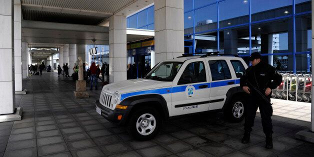 A police officer stands outside the Athens Eleftherios Venizelos International Airport near Athens, Greece,...