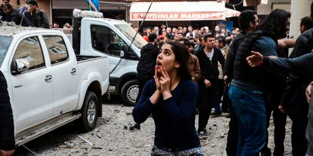 A woman reacts as she looks at the site of a strong blast near the riot police headquarters in the center...