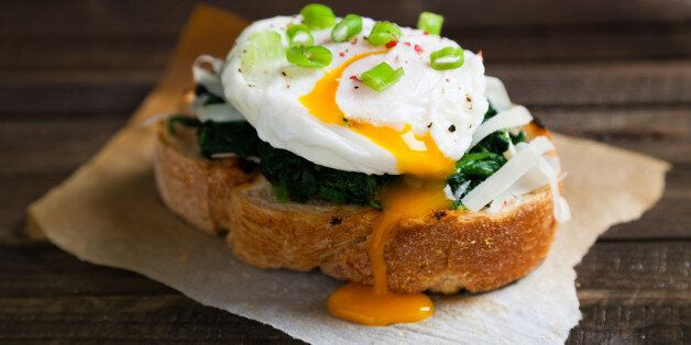 Delicious benedict eggs prepared on a wood table in kitchen