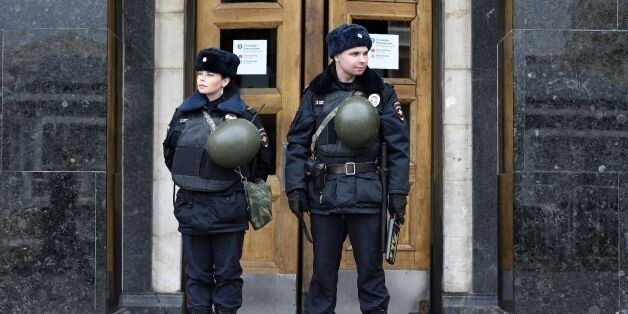 Russian police officers stand guard at the entrance to Ploschad Revolyutsii metro station on April 4,...