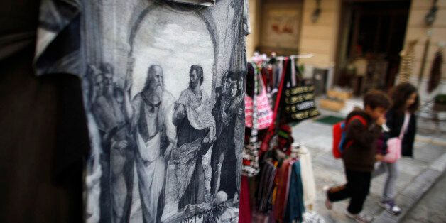 Children pass a souvenir shop displaying a t-shirt with illustrations of the ancient Greek philosophers,...