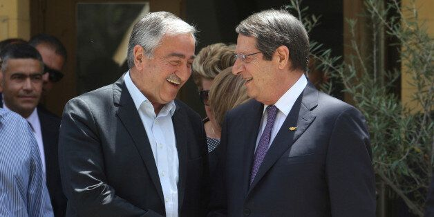 Greek Cypriot leader and Cyprus President Nicos Anastasiades (R) shakes hands with Turkish Cypriot leader...