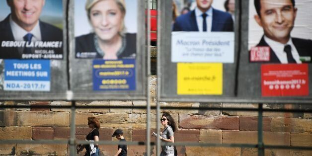 People walk past campaign posters of candidates for the French presidential election on April 10, 2017...
