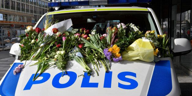 People leaving flowers on a police van outside Ahlens department store following Friday's terror attack...