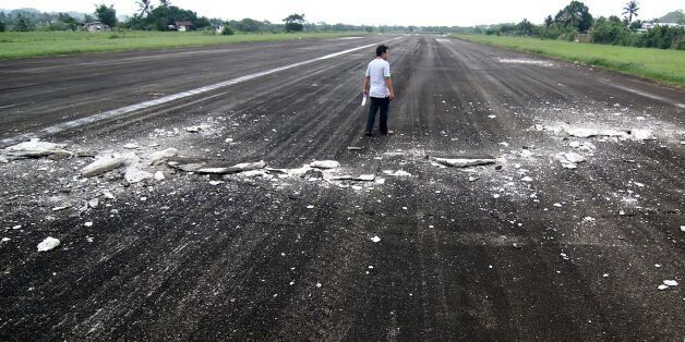 A man walks past the damaged runway of the dometic airport after a 6.5-magnitude earthquake struck overnight...