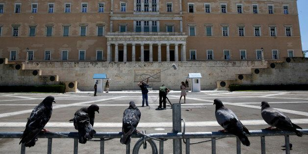Pigeons perch on a police fence as a television crew films in front of the Greek parliament at an empty...