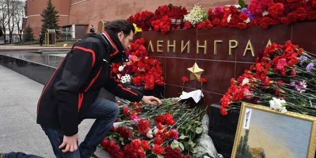 A man lays flowers in honour of the victims of the April 3 blast in the Saint Petersburg metro at a memorial...
