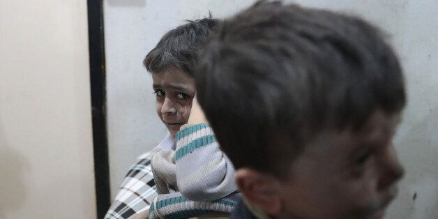 Syrian children wait to receive treatment at a makeshift clinic following reported air strikes by government...