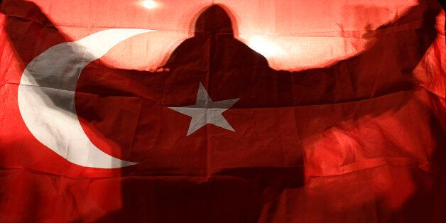 A demonstrator holds a Turkish flag outside the Turkish consulate in Rotterdam where a crowd gathered...