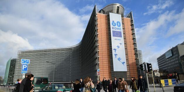 People walk past the European Commission on which is displayed a banner celebrating the 60 years after...